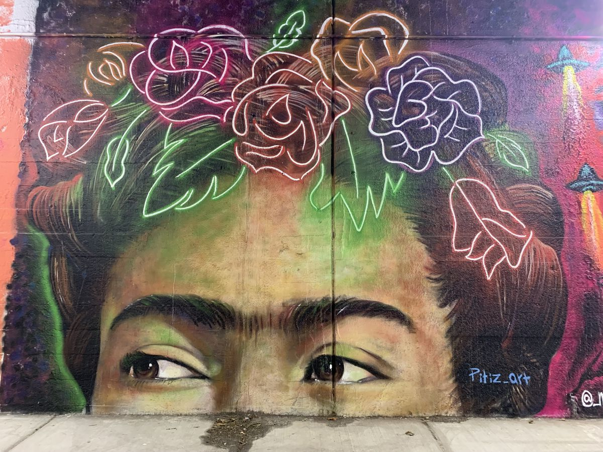 """This mural by East Humboldt Park artist Cecilio Garcia features a portion of Mexican artist Frida Kahlo's face. """"I just grew up knowing her [work] and seeing her paintings, so I wanted to capture her,"""" says Garcia, whose professional name is Pitiz. """"I wanted to keep it super-colorful and more modern by adding the neon touch to it."""""""
