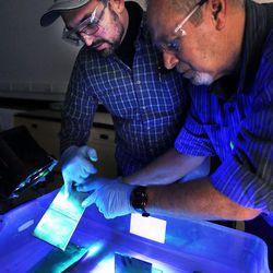 Student Craig Perkins, left, and instructor Kent Hornbeck use a black light to inspect welded plates at Salt Lake Community College's Westpointe Center in Salt Lake City on Wednesday, Dec. 9, 2015.