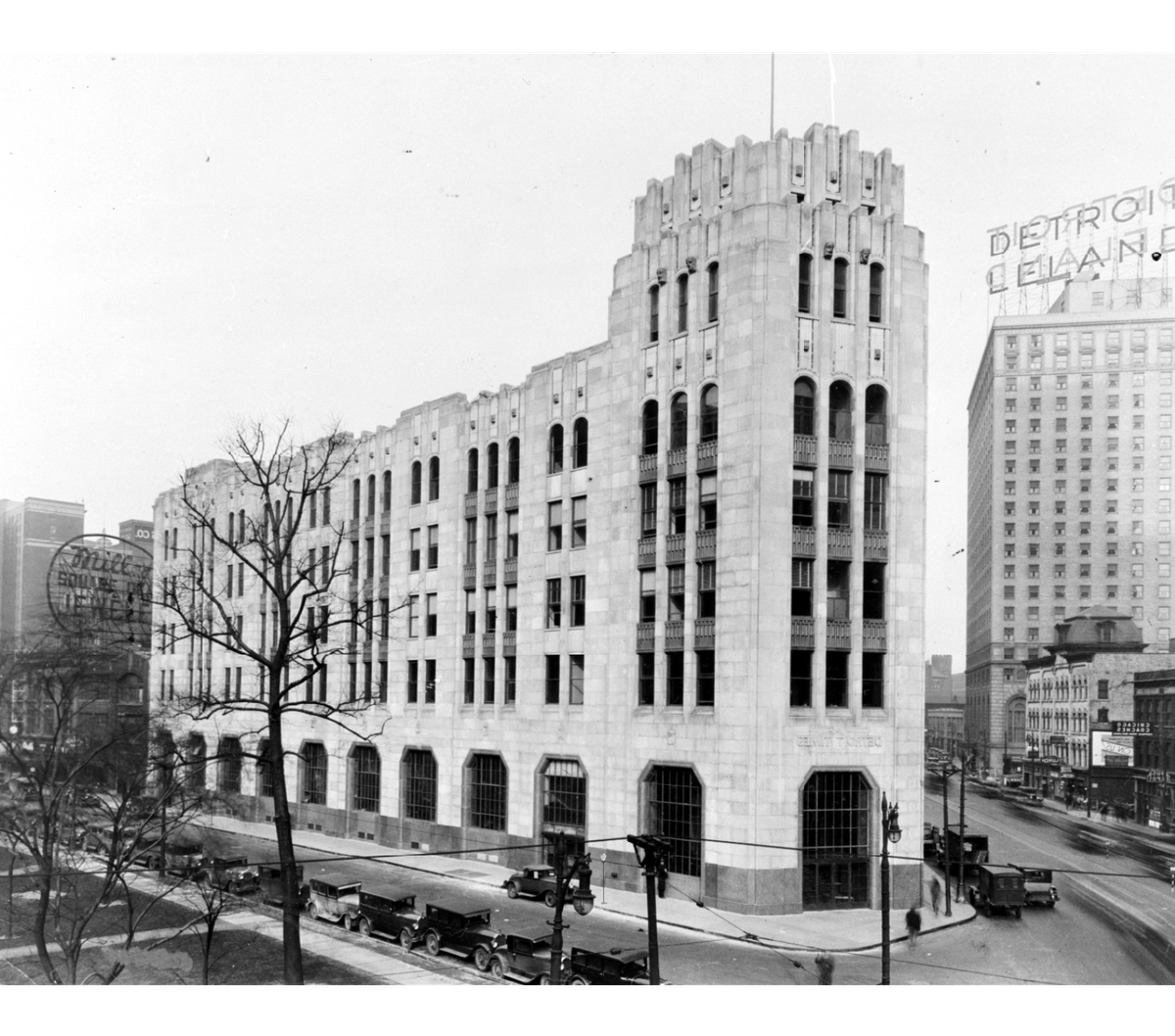 A black and white photo of a long Art Deco building on a triangular lot.