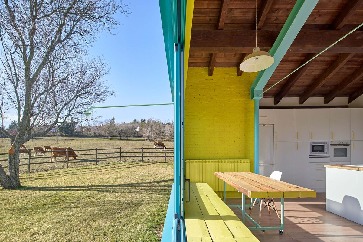 Windows, which feature yellow built-in benches underneath, open to the countryside.