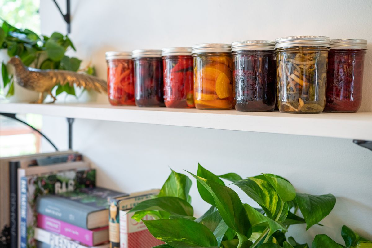 A closeup view of colorful jars filled with fermented fruit and vegetables on a shelf.