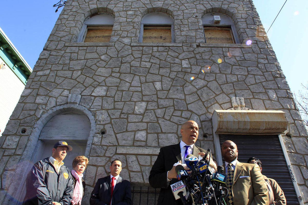 Newark Mayor Cory Booker stands in front of a boarded-up 433 Hawthorne Avenue in Newark, N.J., Friday, April 13, 2012 as he talks about rescuing a neighbor Thursday from a fire at the home.
