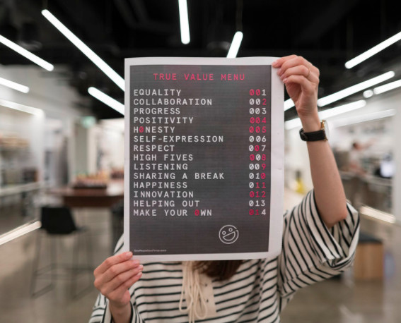 An Uber employee holds up a list of company values that includes equality and happiness,