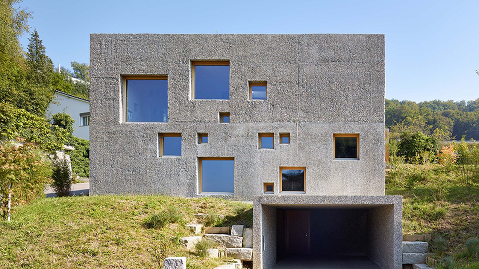 Concrete house in switzerland looks like a block of swiss for Concrete block house