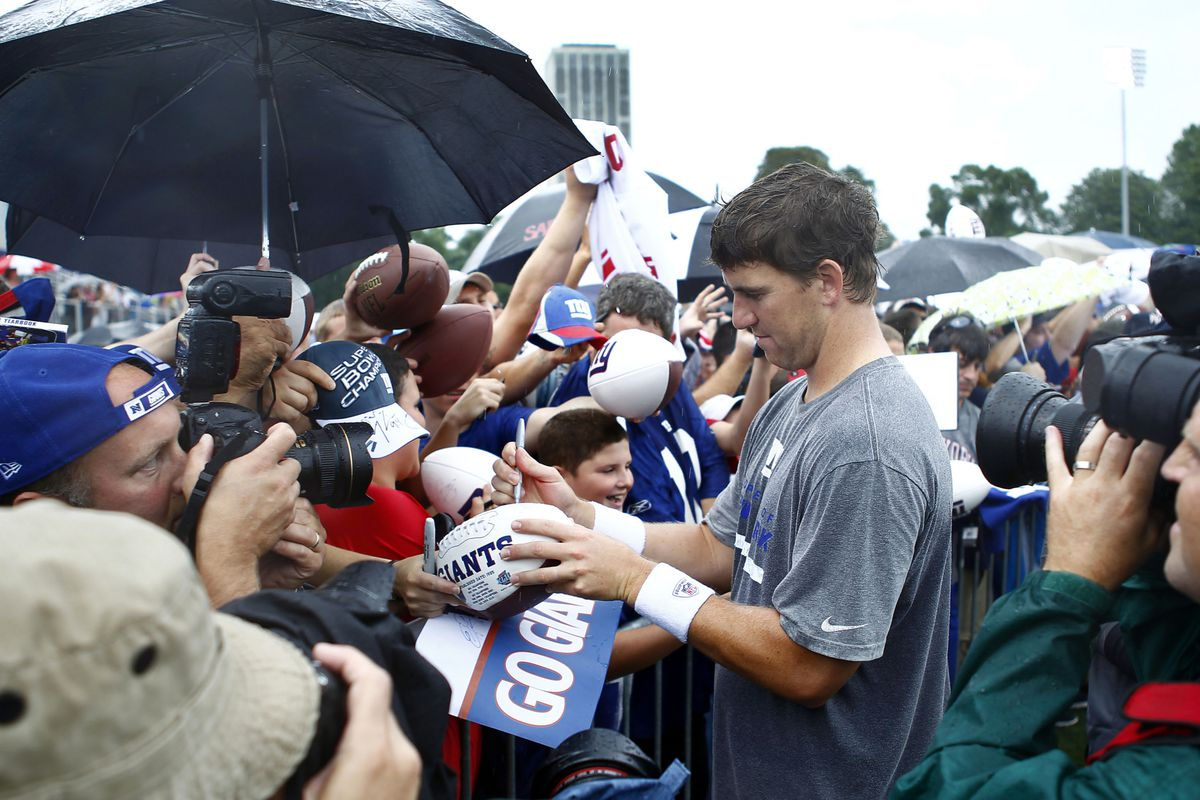 Jul 28, 2012; Albany, NY, USA; New York Giants quarterback Eli Manning (10) signs autographs after training camp at University Field at SUNY Albany. Mark L. Baer-US PRESSWIRE
