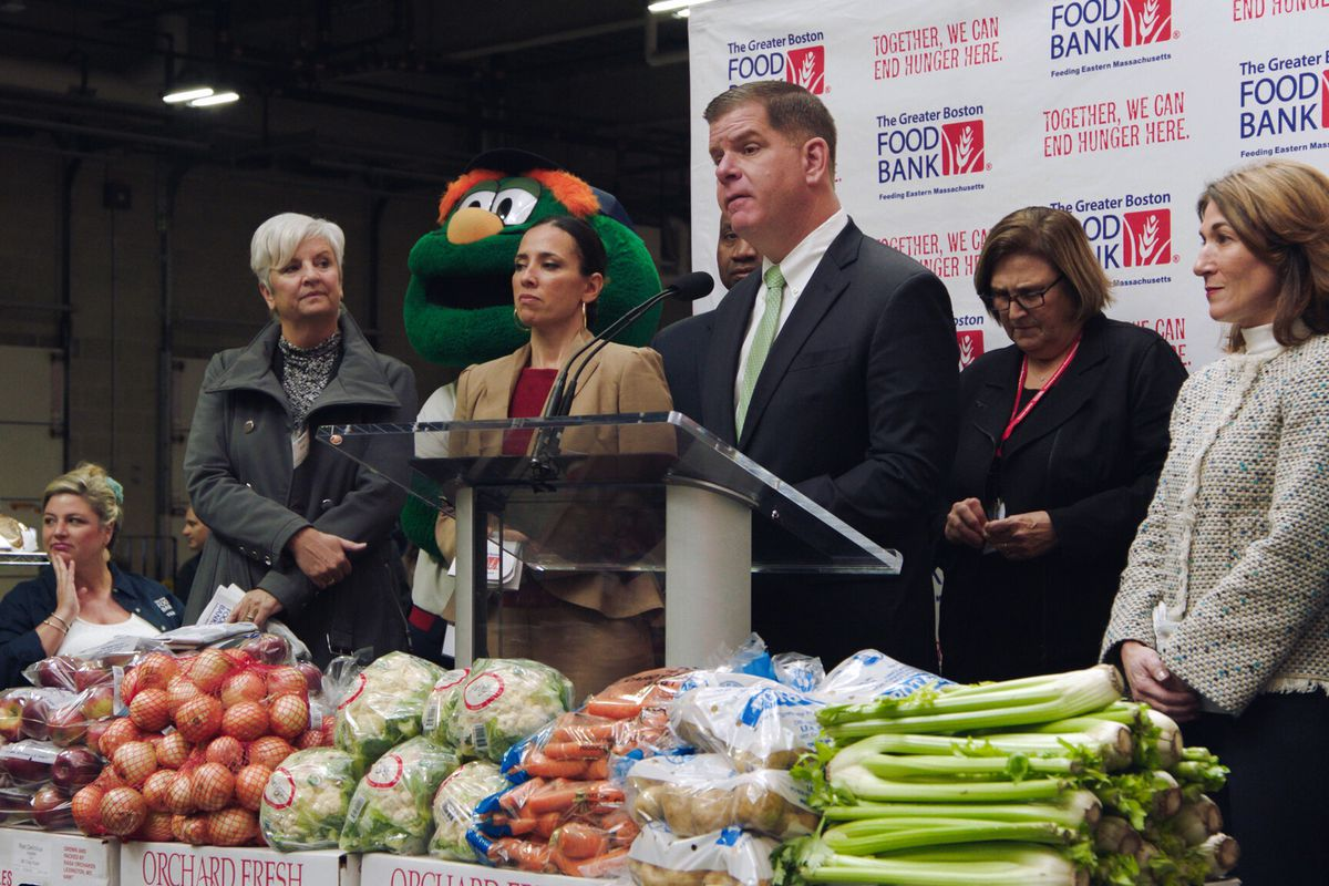 The mayor stands at a podium with several associates, flanked by the Green Monster mascot and piles of vegetables.