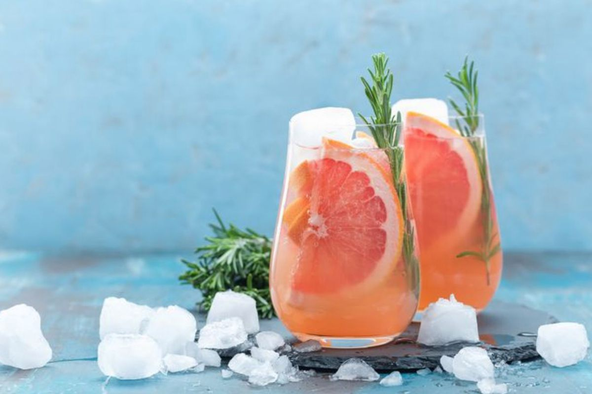 Two glasses filled with non-alcoholic beverages, garnished with rosemary and grapefruit, surrounded by crushed iced.