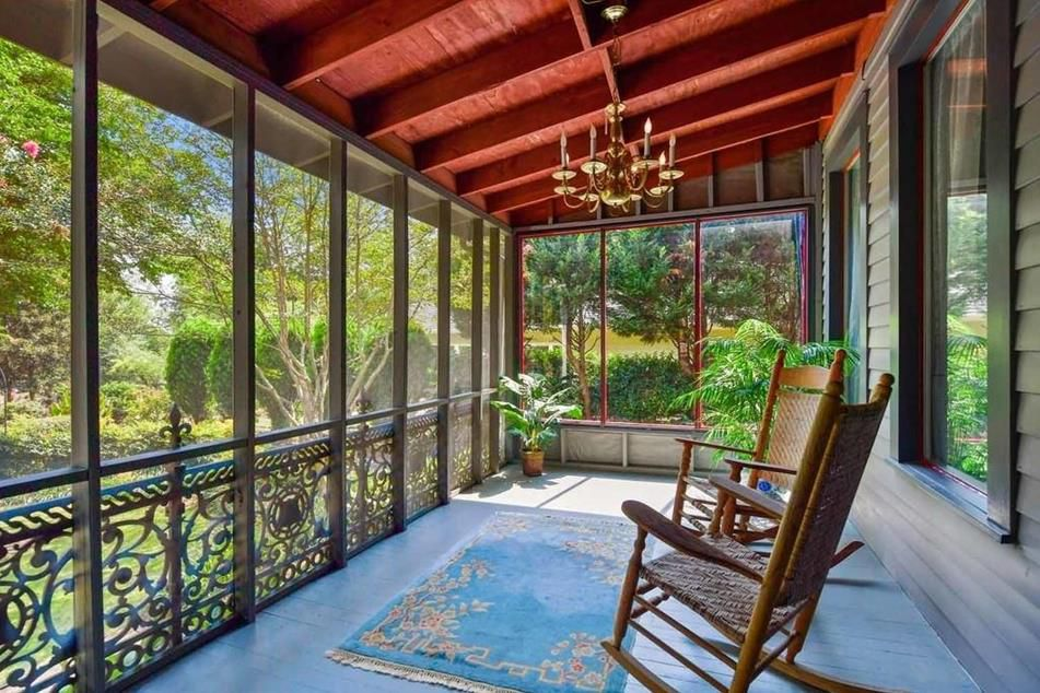 A screened porch with rocking chairs and a chandelier.