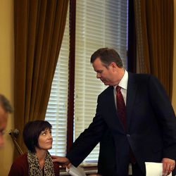 Embattled Utah Attorney General John Swallow shows his wife, Suzanne, a seat before approaching the podium to announce his resignation at the Capitol in Salt Lake City on Thursday, Nov. 21, 2013.