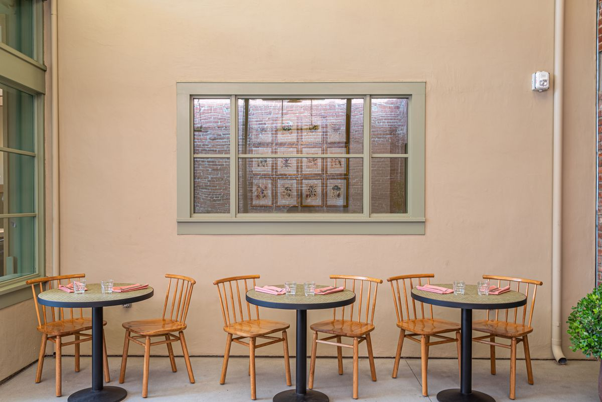 Three small round cafe tables pushed up against a wall, ready for diners to sit in its wooden seats.