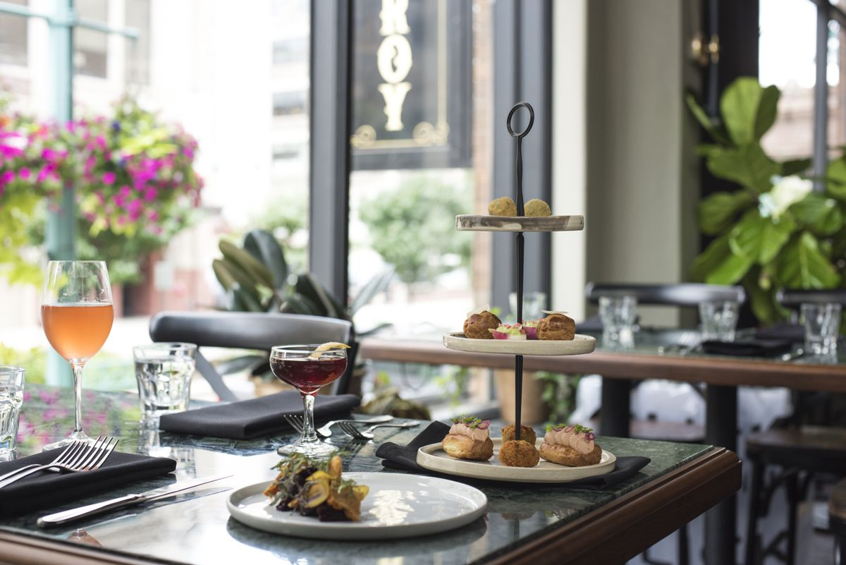 A tower of hors d'oeuvres and glasses of wine on a table at Fauntleroy