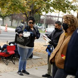 Leo Abila, a social worker with the Salt Lake City Police Department, speaks with a homeless woman about housing options at Taufer Park in Salt Lake City on Friday, Oct. 23, 2020.