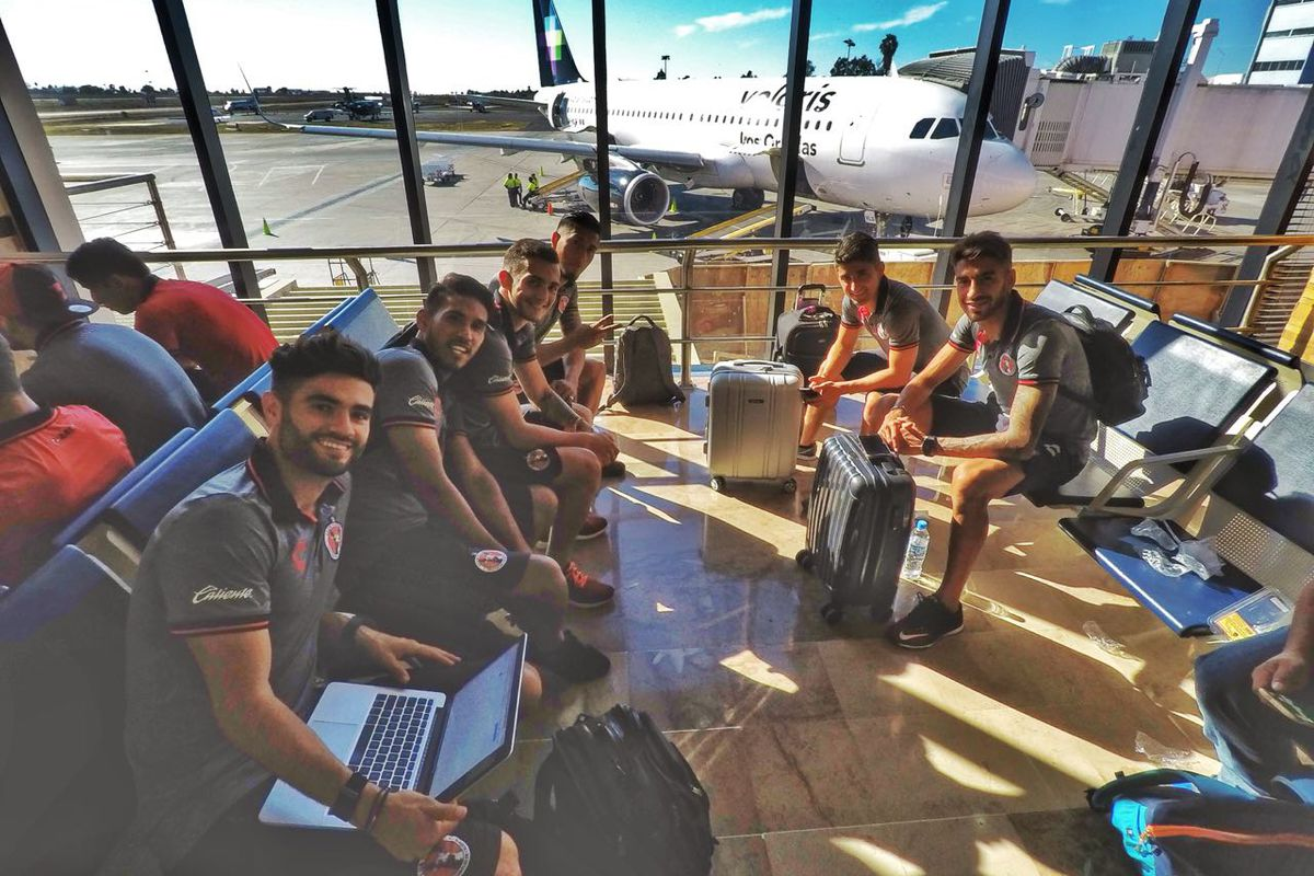 Players from Club Tijuana pose while waiting to board a flight to Puebla to face Lobos BUAP.