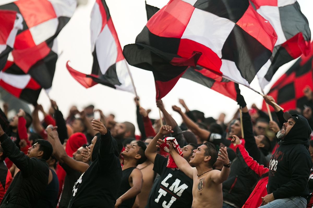 Members of La Masakr3 sing and wave flags during a Club Tijuana match.