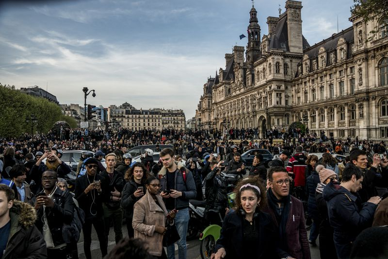Hundreds gather in central Paris to watch smoke and flames rise from a fire at Notre Dame Cathedral on April 15, 2019.