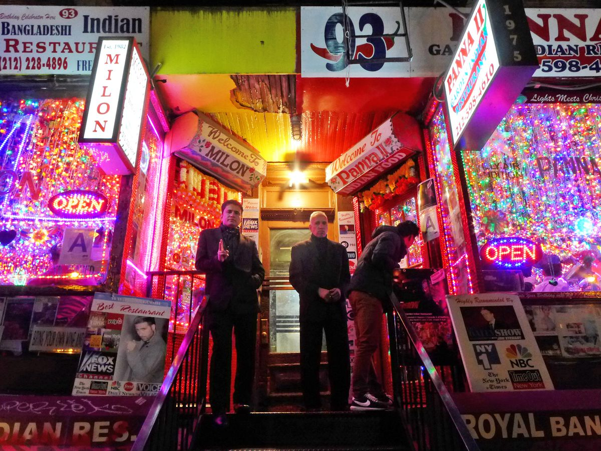 Men stand on the stoop of a colorful restaurant entrance