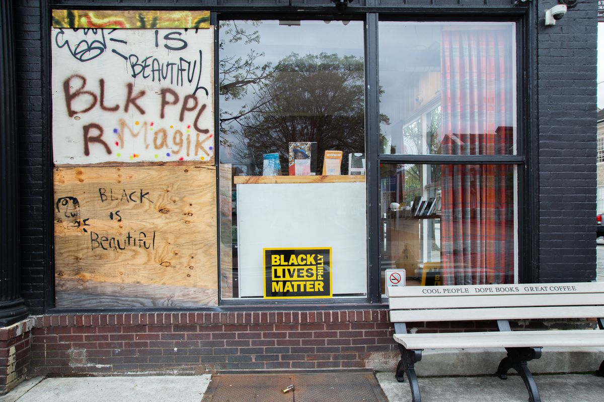 the broken window outside of uncle bobbies that reads blk ppl r magik and black is beautiful