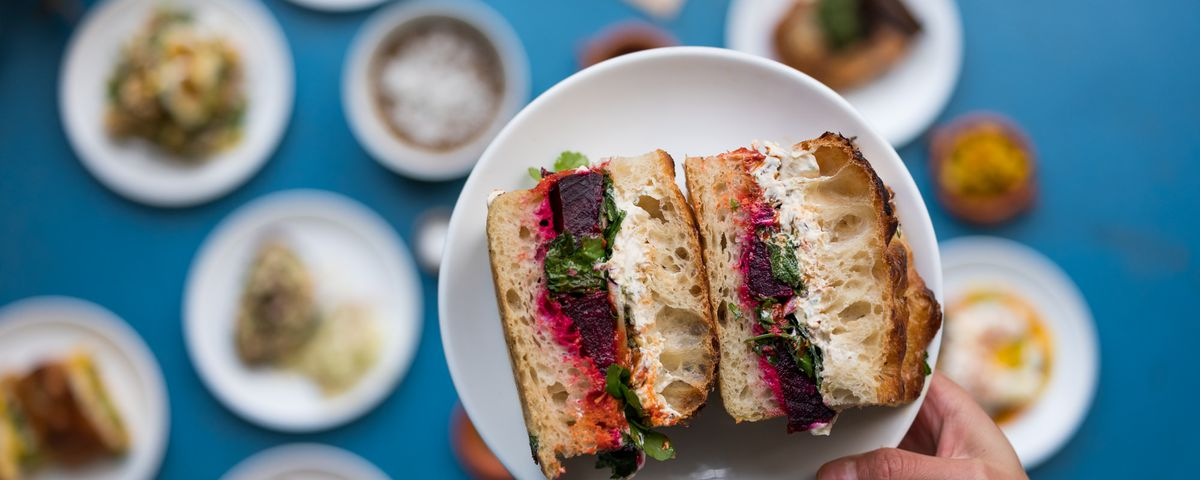 A sandwich held on a white plate with a hand in shot, in focus, with other plates of food below in soft focus on a blue background