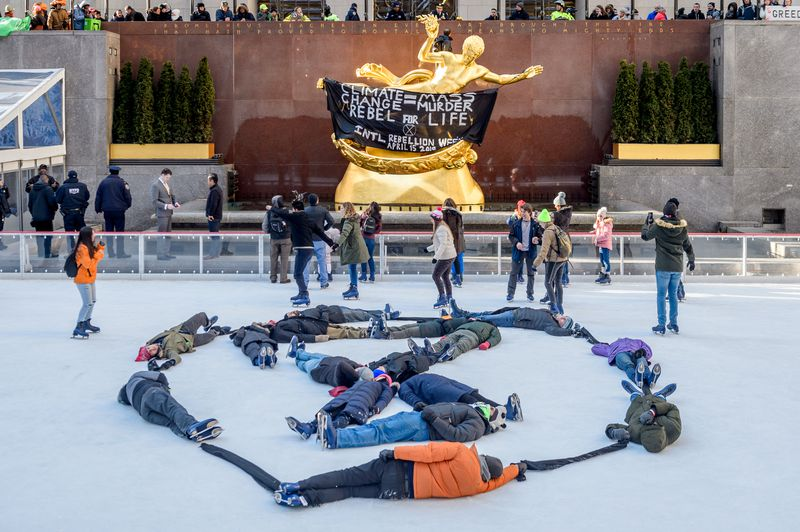 """Protestors lie on the ice rink in Rockefeller Plaza. A sign reads, """"Climate change = mass murder. Rebel for life."""""""