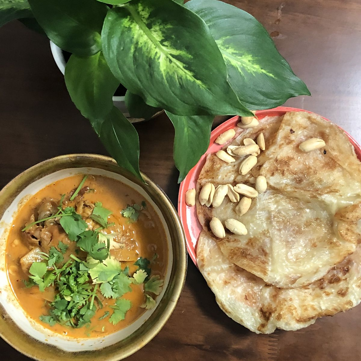 A bowl with an orange curry sitting next to a plate with crispy flatbreads