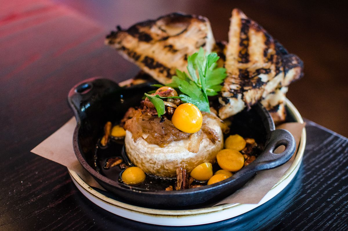 A big ball of brie is displayed in a small cast iron pan, garnished with caramelized onions, big orange gooseberries, and a couple triangles of heavily grilled bread. The dish sits on a black tabletop.