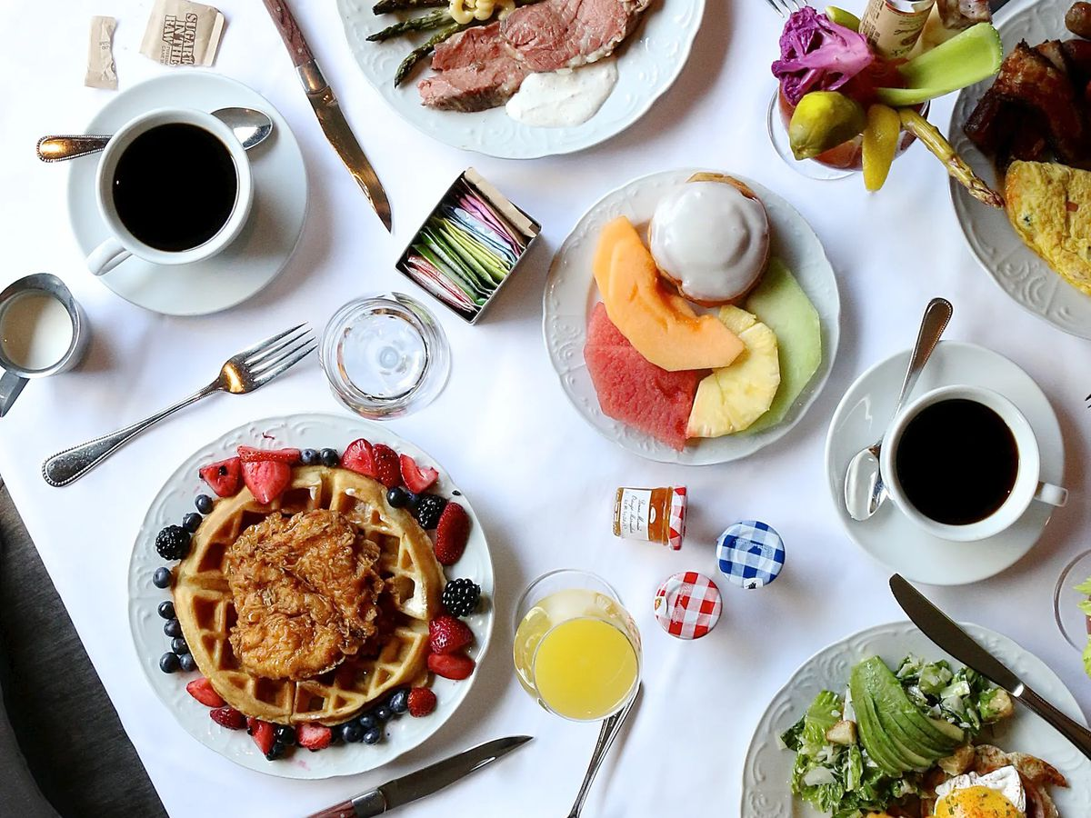 A variety of brunch dishes and beverages spread out on a table.