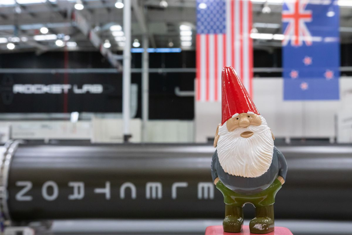 A photo of garden gnome Gnome Chompski standing in front of a rocket