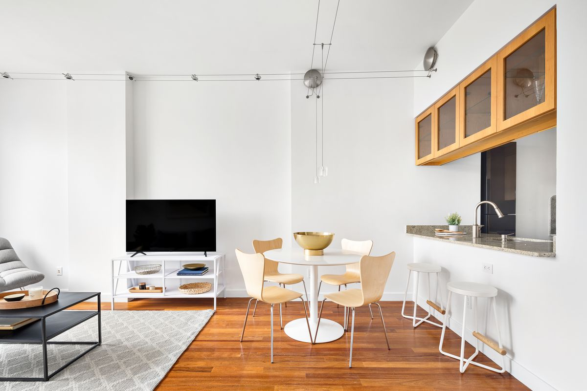 A living area with white walls, hardwood floors, a grey rug, and a round dining table with four chairs.