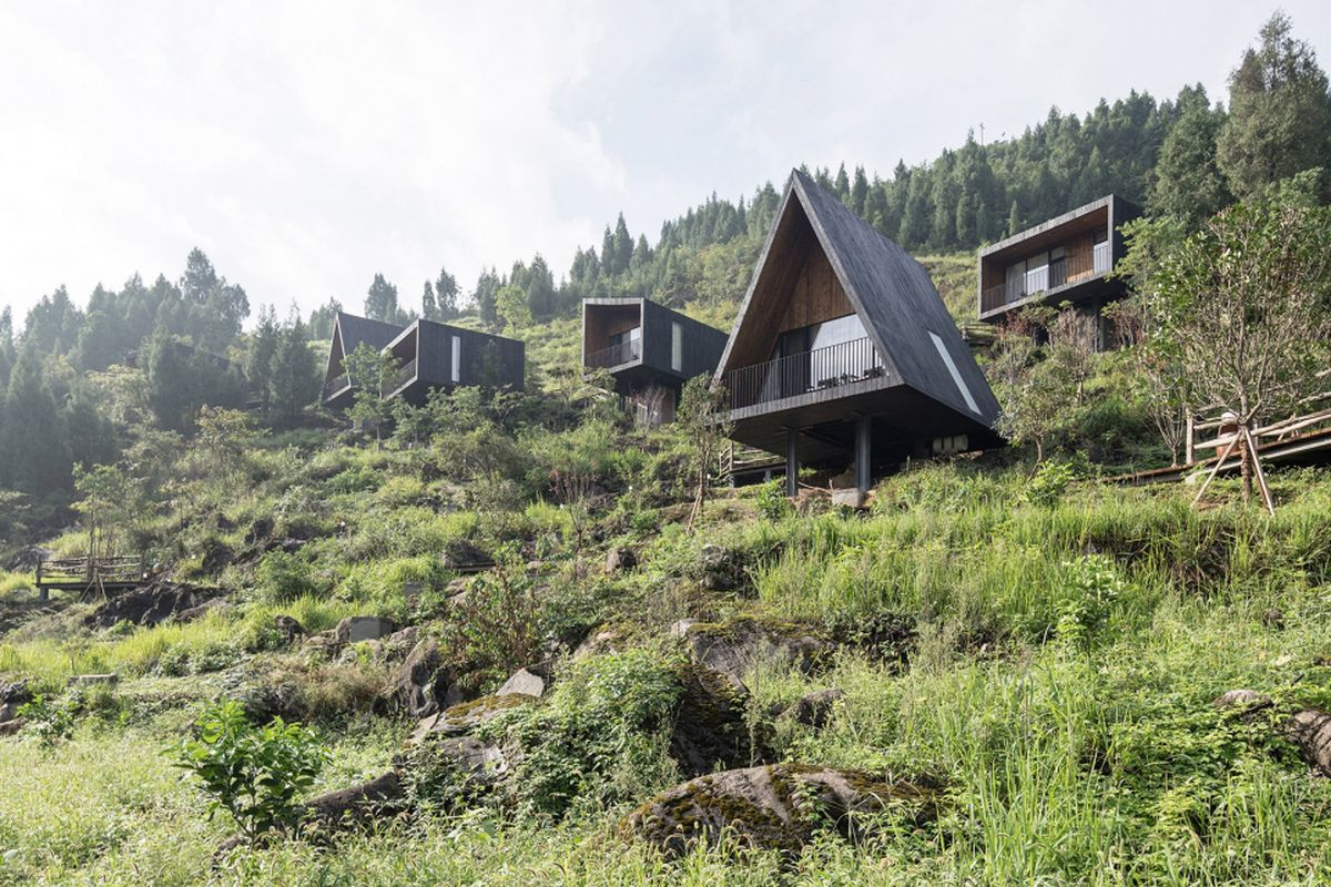 A group of wood cabins with charred wood facades sit in rows on a mountainside in China.