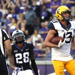 West Virginia wide receiver David Sills V (13) scores on a touchdown pass as TCU cornerback Tony James (28) looks on during the second half of an NCAA college football game Saturday, Oct. 7, 2017, in Fort Worth, Texas. TCU won 31-24.