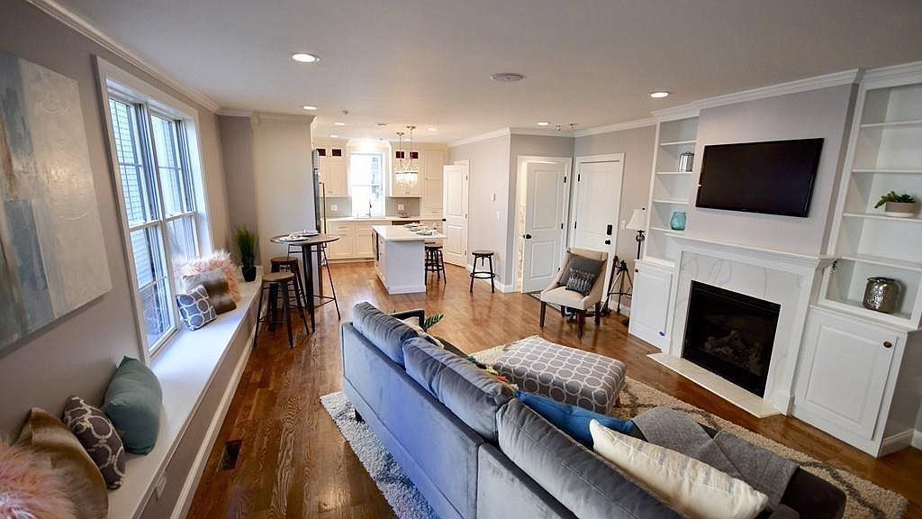 A long living room-kitchen area with furniture.
