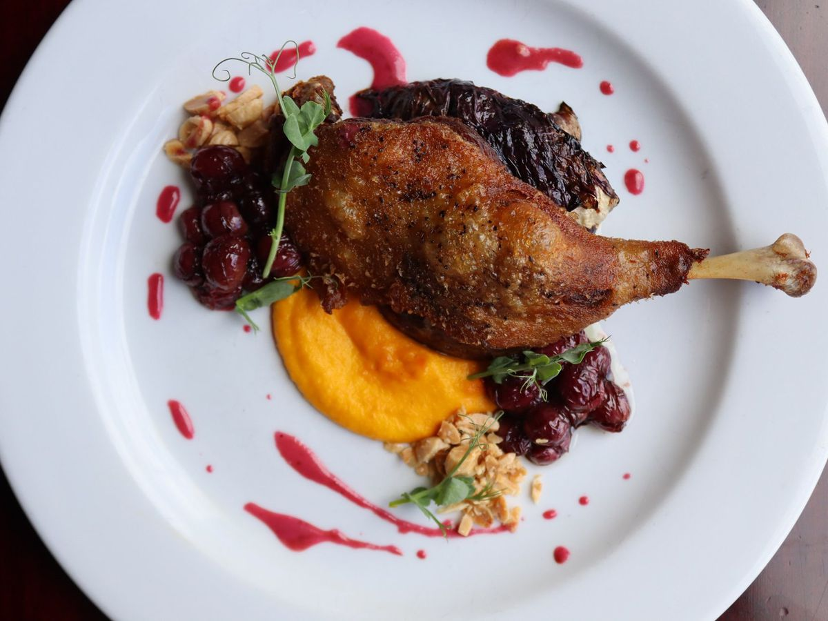 From above, a plate featuring a duck leg in bright orange puree with accoutrements plated around
