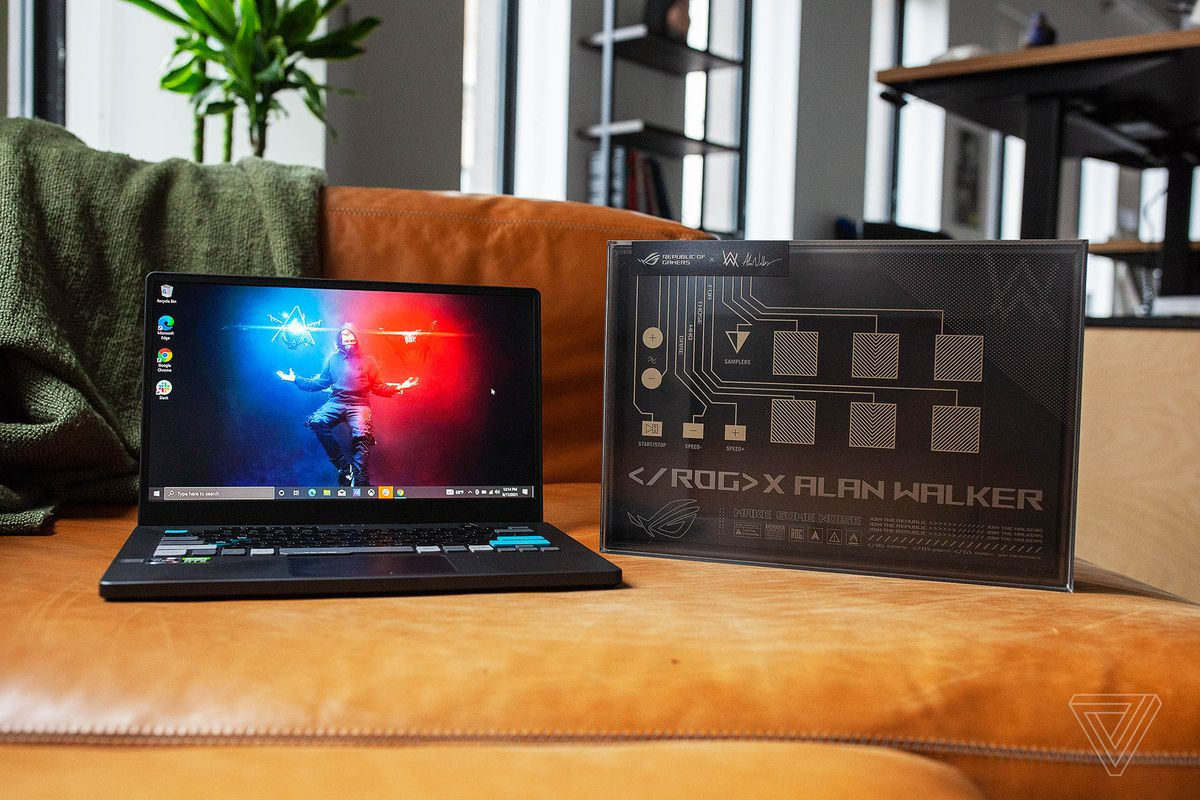 The Asus ROG Zephyrus G14 Alan Walker Edition on a couch seen from the front, open. The screen displays Alan Walker hovering on a red and blue background, conjuring lights of each color with his hands. To its left is its box, with 11 DJ buttons and ROG X ALAN WALKER printed on the bottom.