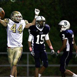 Davis' 44 Troy Hinds celebrates his first half touchdown past Sracuse's 15 Koa Mo'o and 3 Gibby Eidem during the Davis High vs. Syracuse High at Syracuse High School on Friday, September 16, 2011.