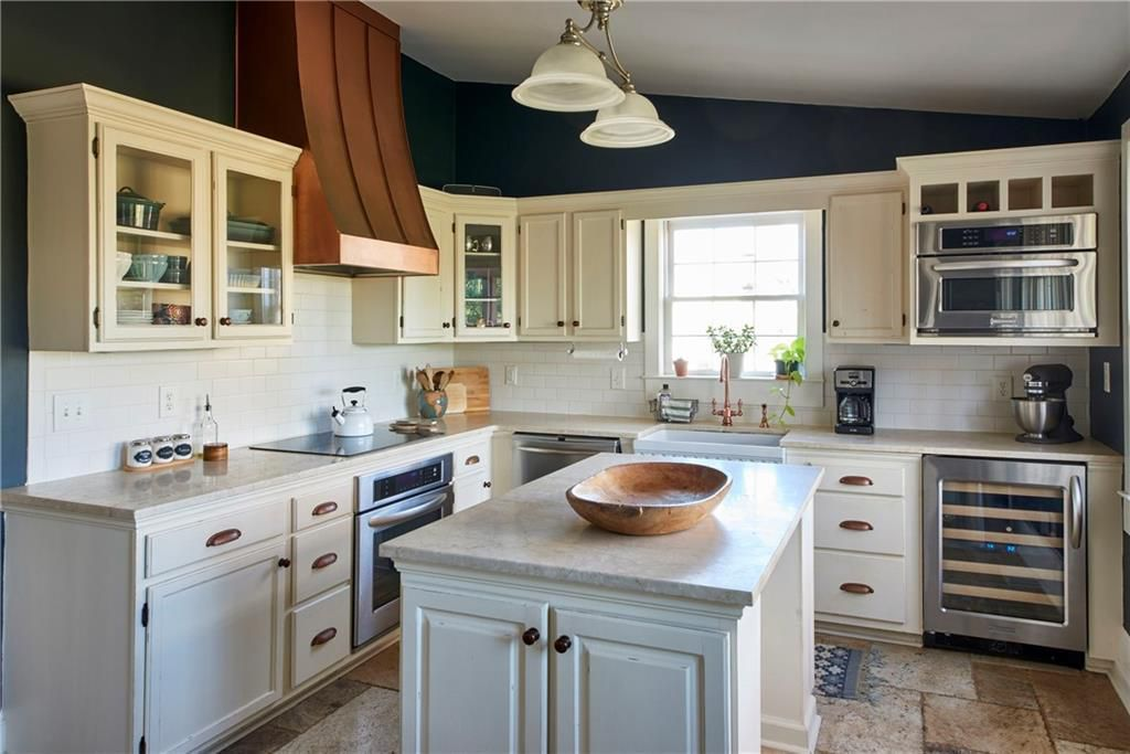 A white kitchen space with stainless appliances.