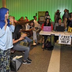 """While activists and lawyers at the table at right offer help and information, Hanadi Al-Haj prays in the Tom Bradley International Terminal at Los Angeles International Airport as she waits for her Yemeni mother to arrive from Jordan via Istanbul, Thursday, June 29, 2017, in Los Angeles. The Trump administration's travel ban temporarily barring some citizens of six majority-Muslim countries from coming to the United States in now in place. The ban is entering into force because of a Supreme Court opinion this week. The new rules stop people from Syria, Sudan, Somalia, Yemen, Iran and Libya from getting a visa to the United States unless they have a """"bona fide"""" relationship with a close relative, school or business in the U.S."""