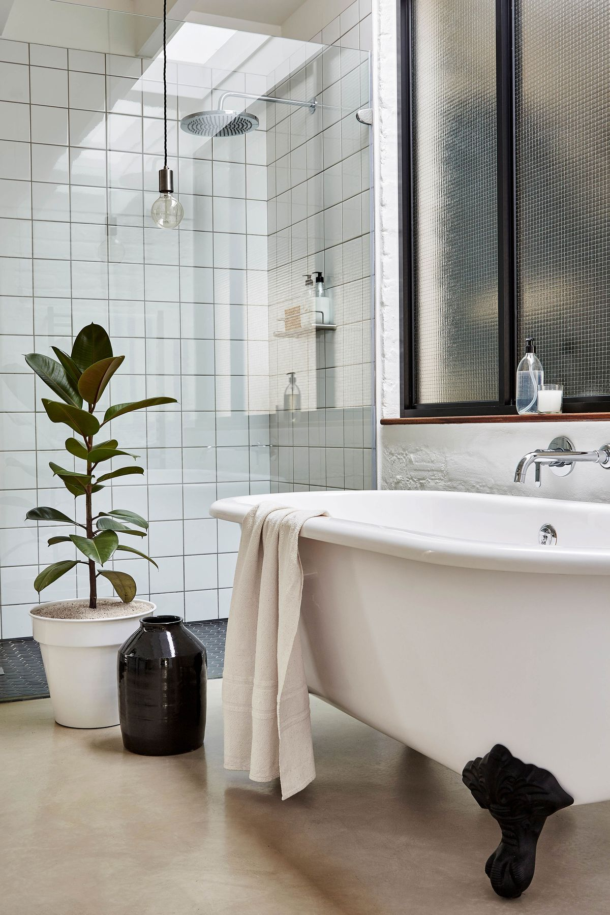 A bathroom with a clawfoot tub and a glass shower, also has a concrete floor.