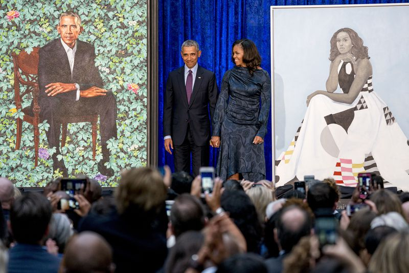 In this Feb. 12, 2018, file photo, former President Barack Obama and former first lady Michelle Obama stand on stage together as their official portraits are unveiled at a ceremony at the Smithsonian's National Portrait Gallery in Washington. The portraits will begin a five-city national tour in Chicago on June 18, 2021.