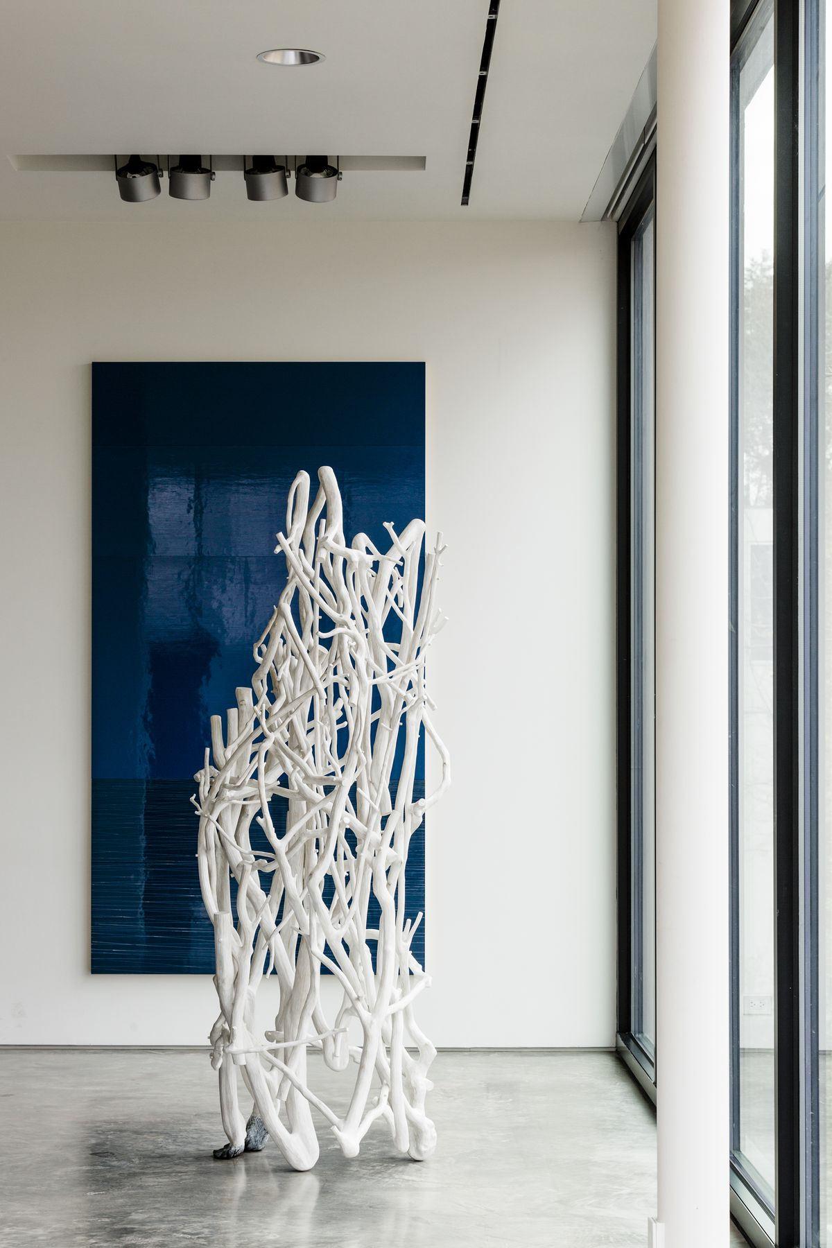 A large, white, twig-like sculpture stands next to a window.