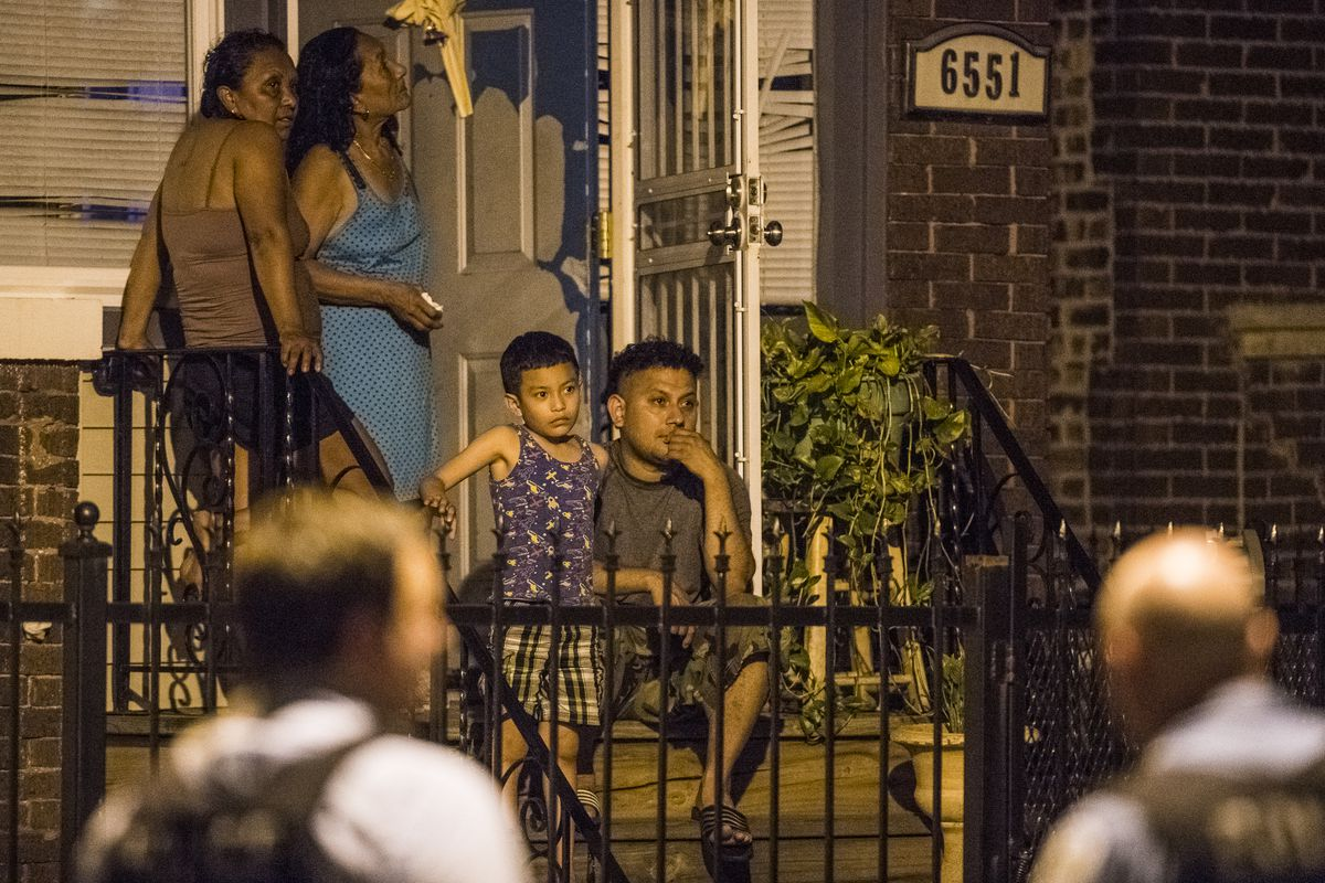 A family sits on their porch as police investigate the scene of a person shot and killed Sunday night in the 6500 block of South Maplewood in Chicago. The person was shot and killed in front of this families home.   Tyler LaRiviere/Sun-Times