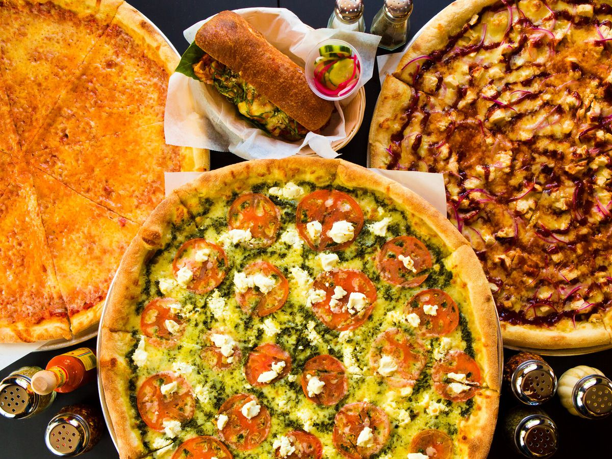 Overhead shot of a spread of pizzas, accoutrements, and a sandwich on a dark table