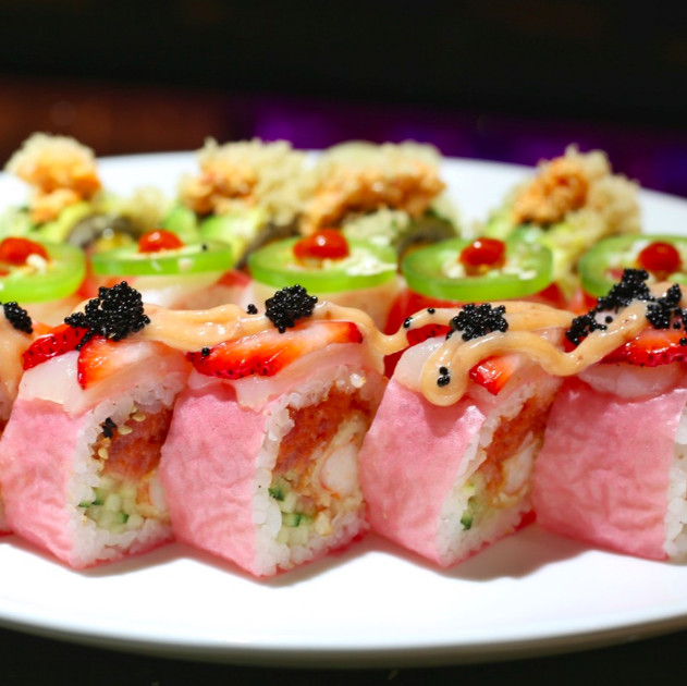 Several sushi rolls are lined up on a white plate