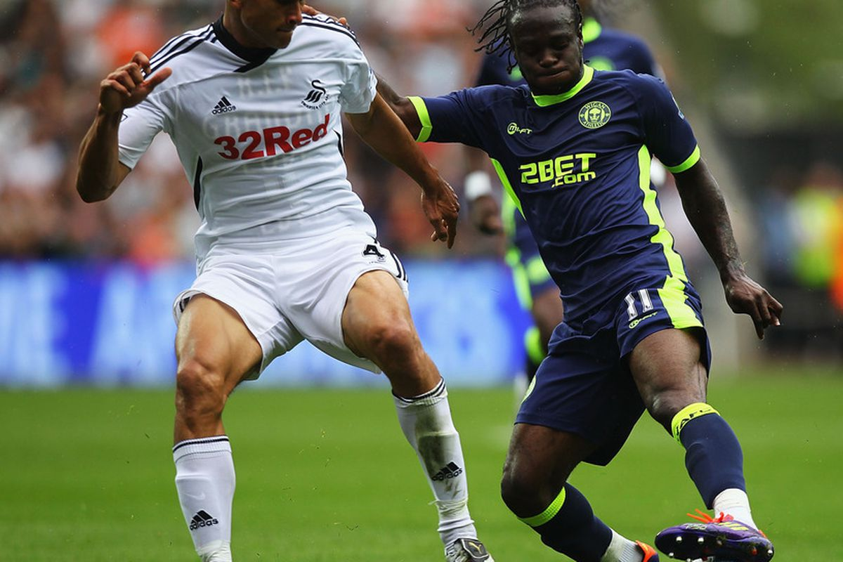 Victor Moses of Wigan and Steven Caulker of Swansea challenge for the ball during the Barclays Premier League match between Swansea City and Wigan Athletic at Liberty Stadium.