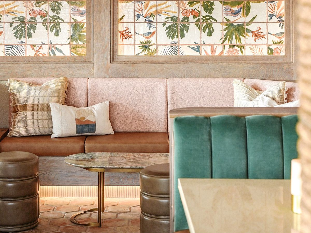 Banquette seating against a wall with a floral tile mural and light fixture overhead made of multiple fans.