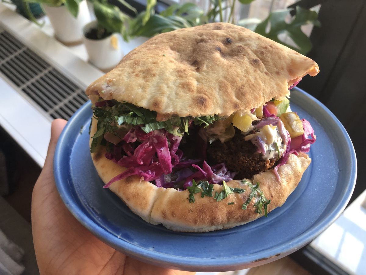A hand is holding a blue plate with a sandwich on it that contains some red beets, pickles, and crispy brown falafel