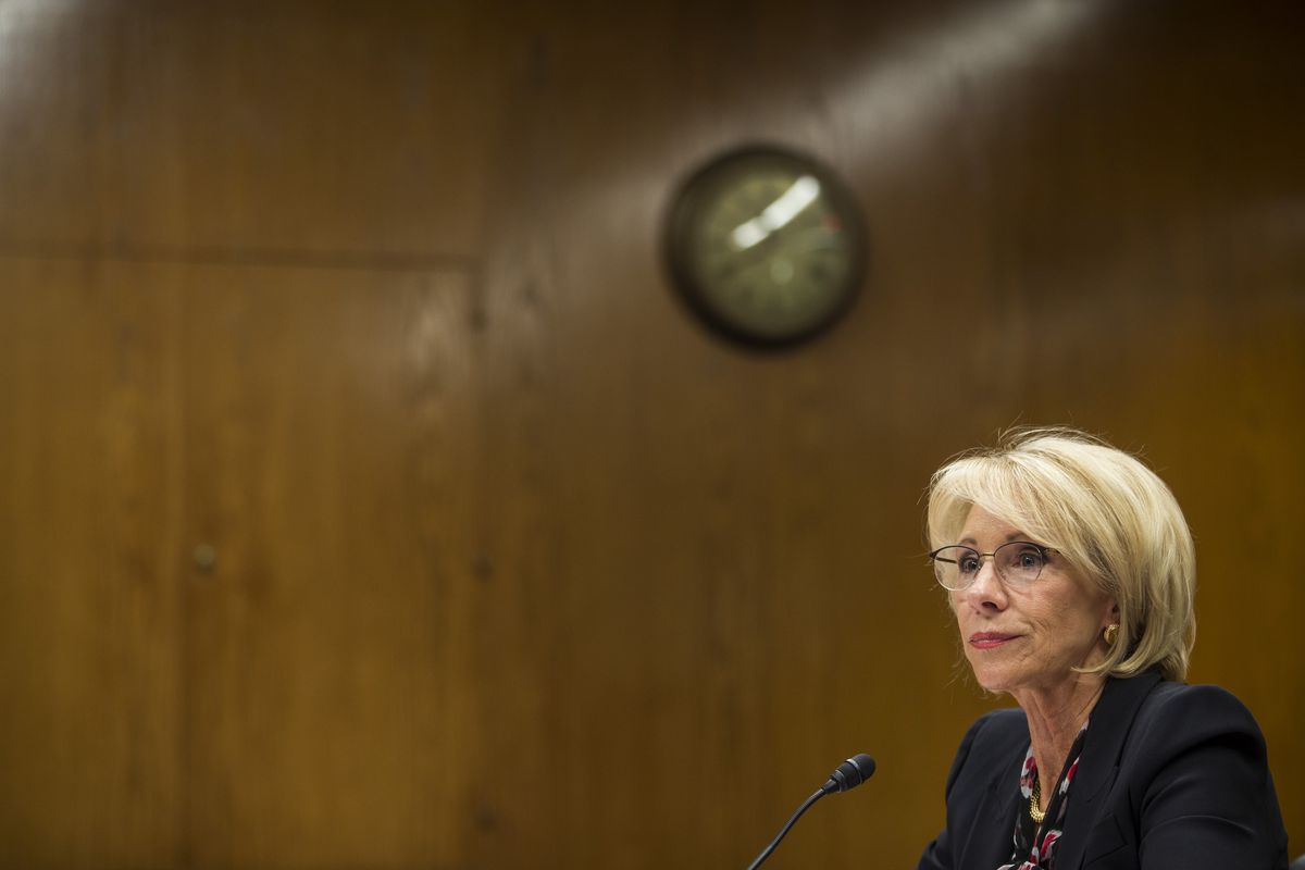 Department of Education Secretary Betsy DeVos seated before a microphone.
