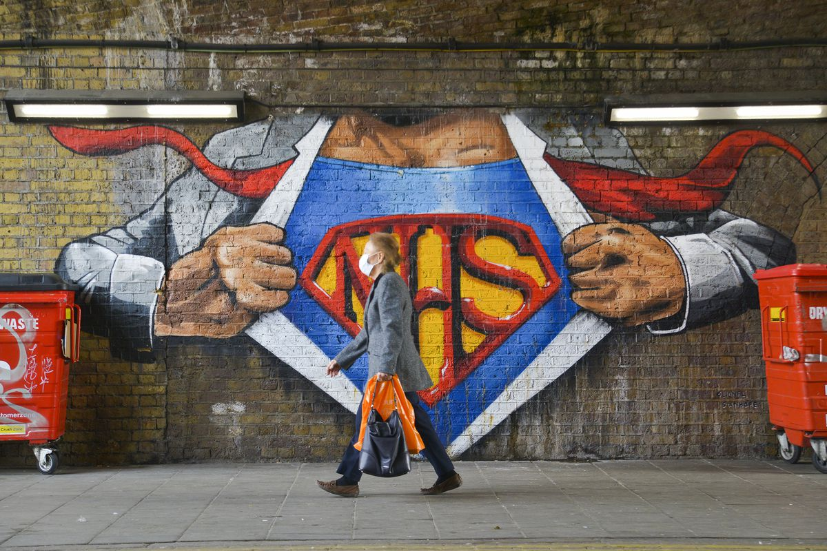 A woman wearing a face mask as a precaution against the spread of Covid-19 walks past a Superman graffiti tribute to the NHS in Waterloo.