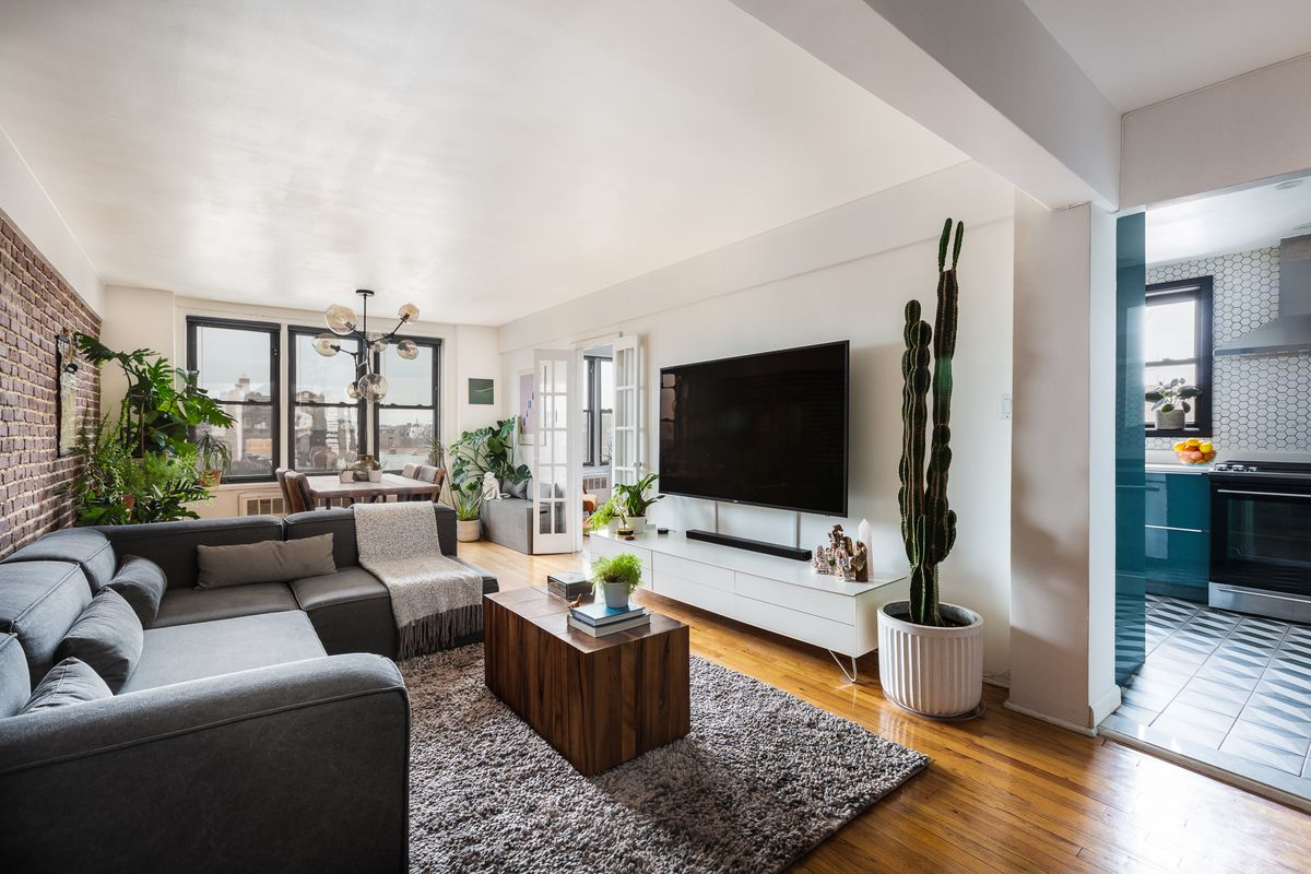 A living room area with hardwood floors, a brown rug, exposed brick, and a dark grey couch.