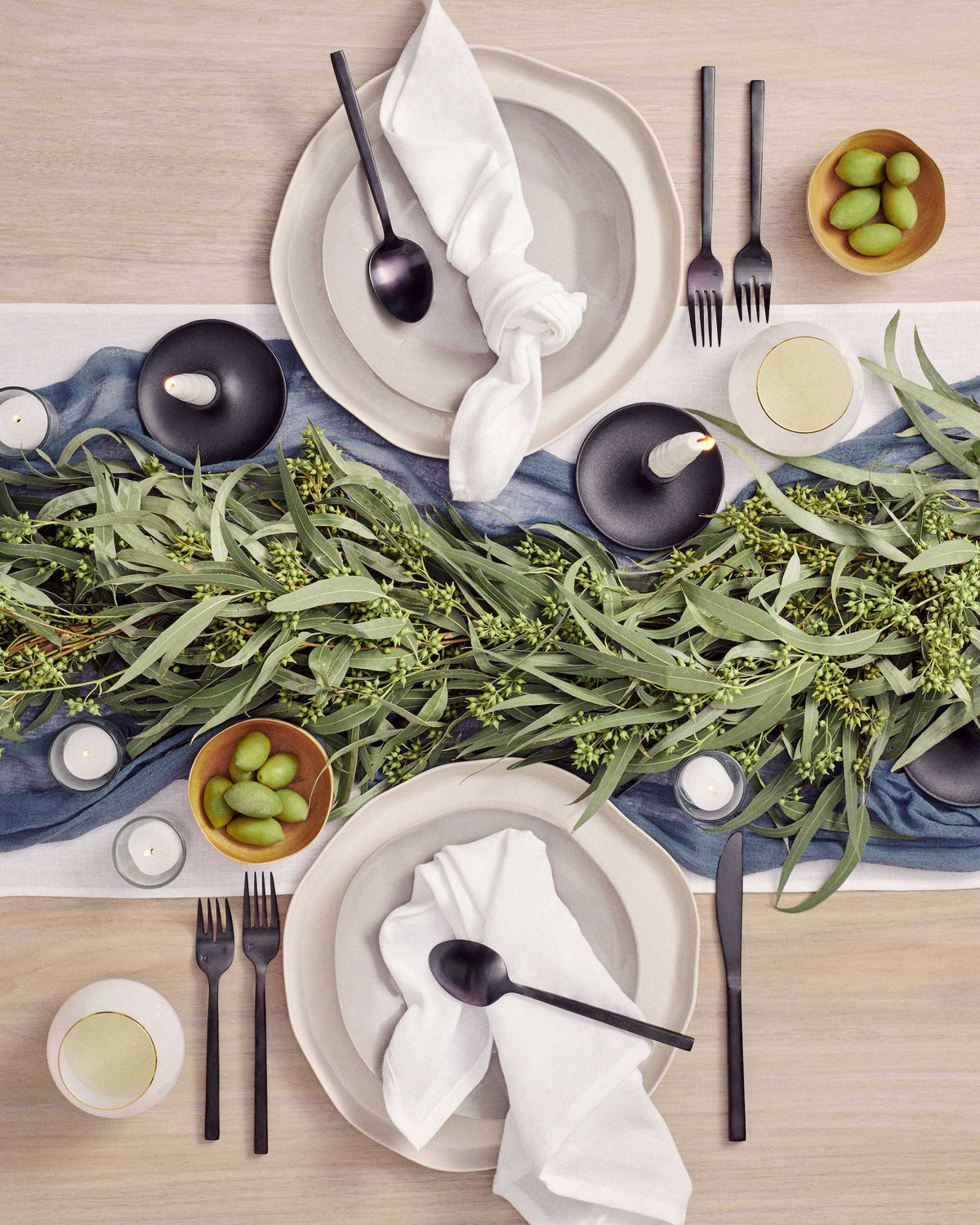 An overhead view of a table setting with off-white plates, black candle holders and flatware, and a greenery runner.