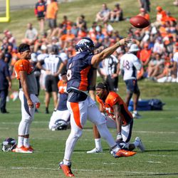 Quarterback for the Broncos Chad Kelly works his arm some more while the team stretches.